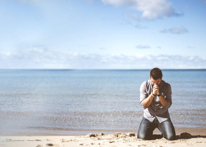 Man kneeling on beach