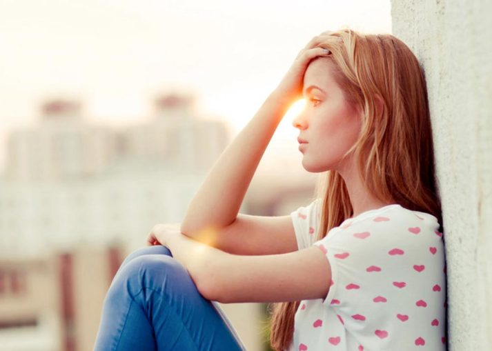 Girl sitting against wall