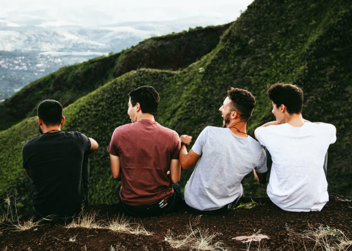 young men laughing sitting on hill