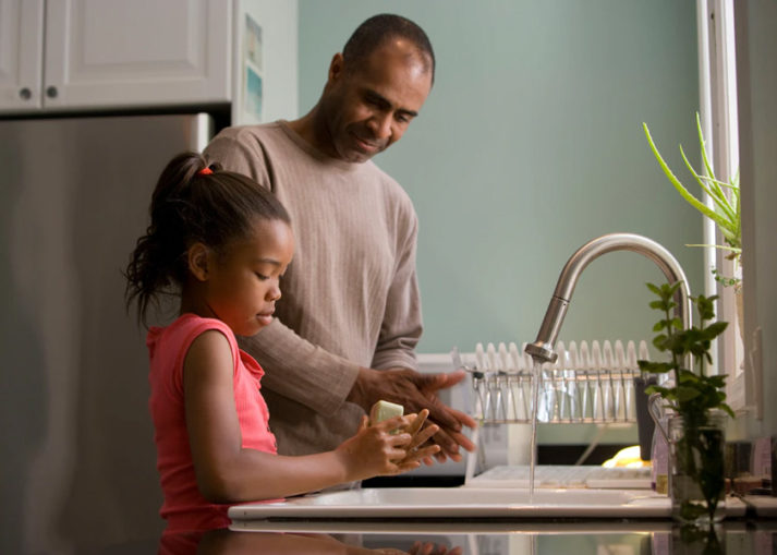This African-American father was shown in the process of teaching his young daughter how to properly wash her hands